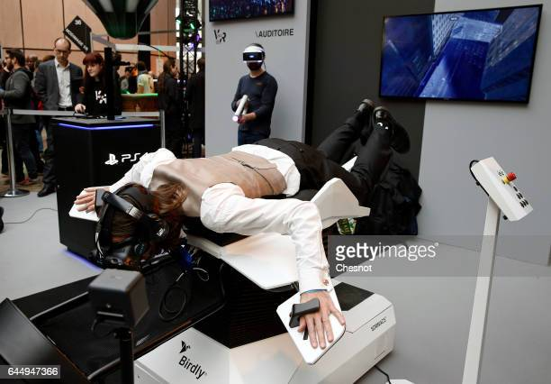 A visitor plays a video game 'Birdly' with the virtual reality headset 'HTC vive' to experience 3D virtual reality during the show 'Virtuality Paris...