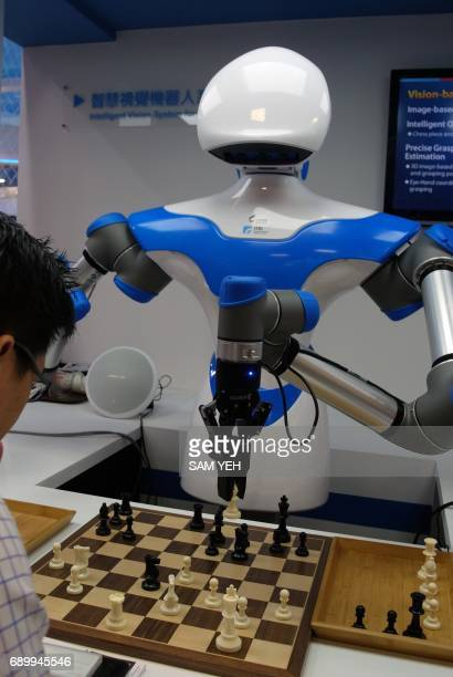 A visitor plays chess with a robot designed by Taiwan's Industrial Technology Research Institute during the Computex Show in Taipei on May 30 2017...