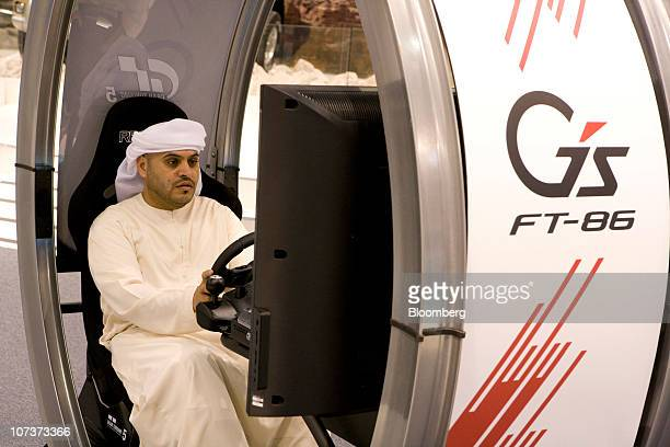 A visitor plays the Gran Turismo 5 video game on the Toyota Motor Corp stand at the Abu Dhabi International Motor Show in Abu Dhabi United Arab...