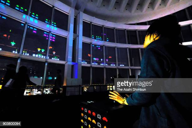 A visitor plays the 'Space Invaders Giga Max' projected on the window of the Roppongi Hills during the press preview on January 11 2018 in Tokyo...