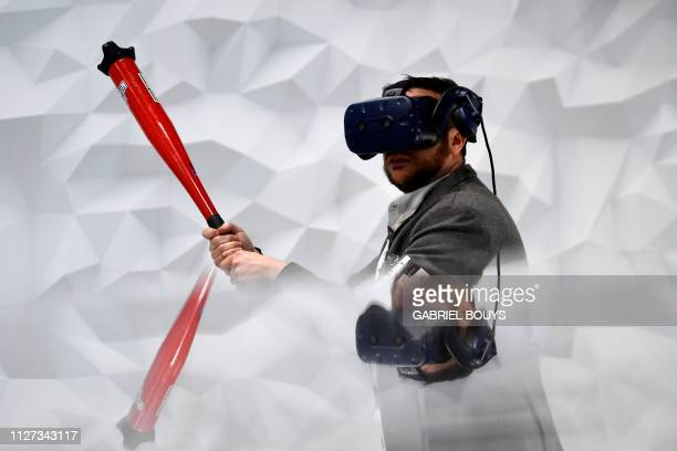 A visitor plays virtual baseball with the Vive Pro Eye virtual reality headset at the Mobile World Congress in Barcelona on February 25 2019 Phone...