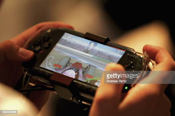 A visitor plays with a Sony 'PSP' at the Computer Gaming Convention on August 18 2005 in Leipzig Germany The convention is Germany's largest fair for...