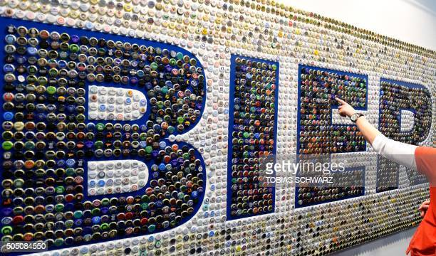 A visitor points at an installation made of crown caps reading 'Beer' at the opening day of the 'Gruene Woche' agricultural fair in Berlin on January...