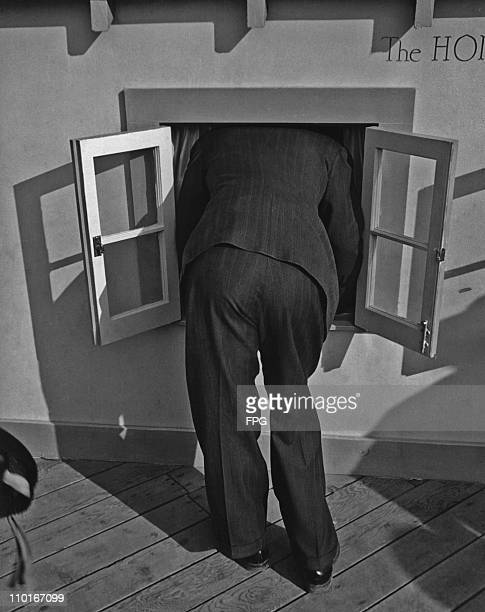 A visitor pokes his head in through the window of one of the buildings in a 'midget village' USA circa 1940