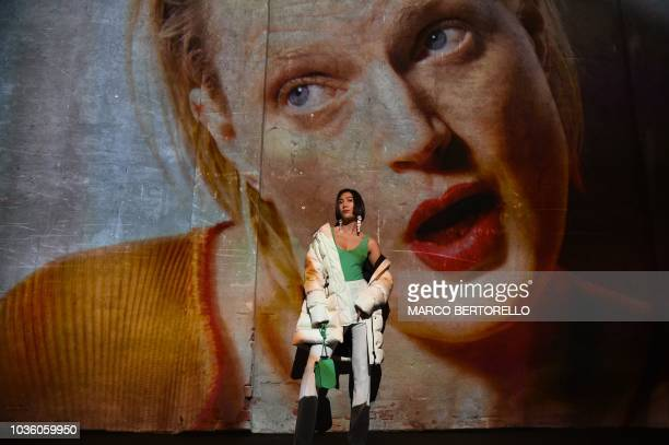 A visitor poses during a video presentation of creations by Moncler fashion house during the Women's Spring/Summer 2019 fashion shows in Milan on...
