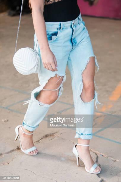 A visitor poses fashion detail torn pants during Sao Paulo Fashion Week N45 SPFW Summer 2019 at Brazilian Cultures Engineer Armando de Arruda Pereira...