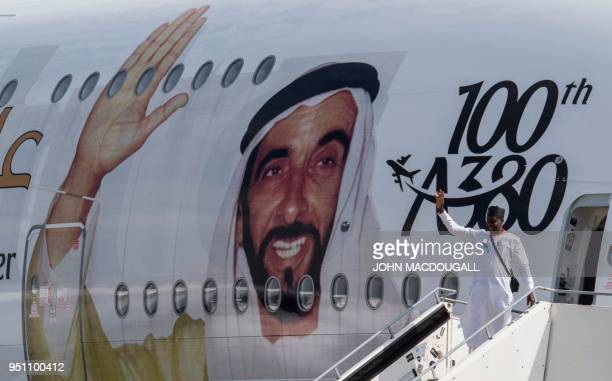 A visitor poses for a photo in front of an Emirates A380 Airbus passenger aircraft decorated with a giant portrait of UAE founding father Zayed bin...