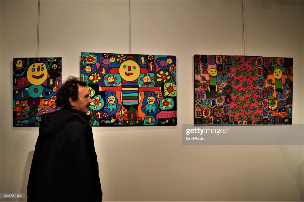 A visitor poses for a photo next to paintings by Turkish painter