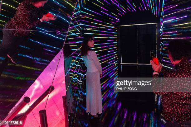 A visitor poses for a photograph inside a kaleidoscope installation erected as part of Christmas festivities at a shopping arcade in Hong Kong on...