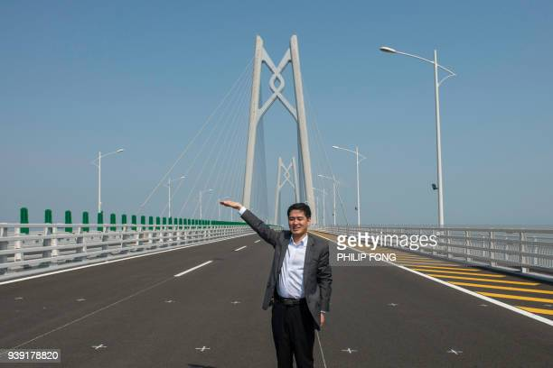 A visitor poses for a photograph on a section of the Hong KongZhuhaiMacau Bridge in Zhuhai on March 28 2018 Officials say the bridge billed as the...