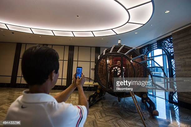 A visitor poses for a photograph with an art installation at Studio City casino resort developed by Melco Crown Entertainment Ltd in Macau China on...