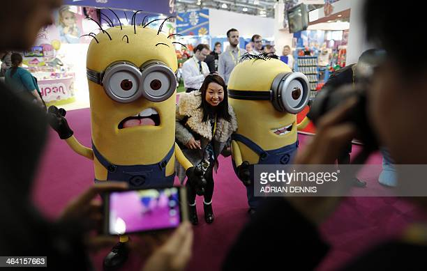 A visitor poses for a photograph with people dressed as giant Minions characters during a photocall for the annual Toy Fair at the Olympia exhibition...
