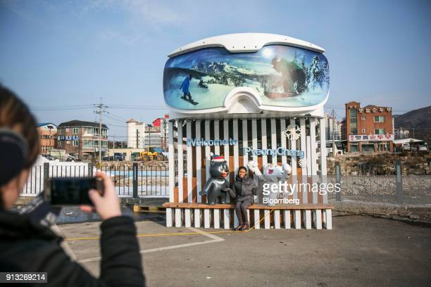 A visitor poses for a photograph with statues of the 2018 PyeongChang Winter Olympic Games mascot Soohorang right and Paralympic Games mascot Bandabi...