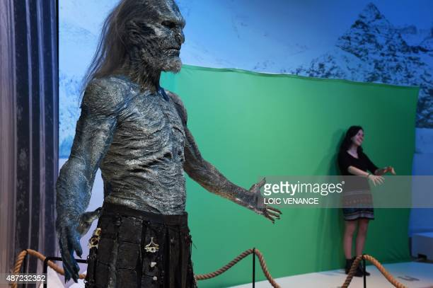 A visitor poses for a picture against a green screen next to a model of a White Walker character during the opening of an exhibition dedicated to...