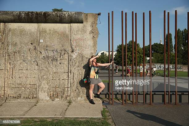 A visitor poses for a snapshot at a surviving section of the Berlin Wall at the Bernauer Strasse memorial on August 6 2014 in Berlin Germany Germany...