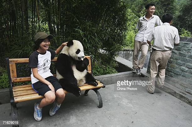A visitor poses for pictures with a giant panda cub she adopted at the China Wolong Giant Panda Protection and Research Centre on August 8 2006 in...