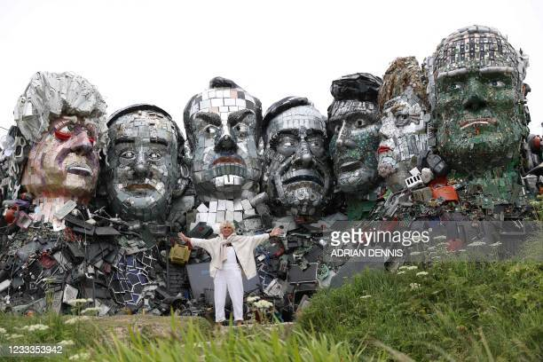 Visitor poses in front of a giant Mount Rushmore-style sculpture of the G7 leaders heads, made entirely of discarded electronics, on a beach near to...