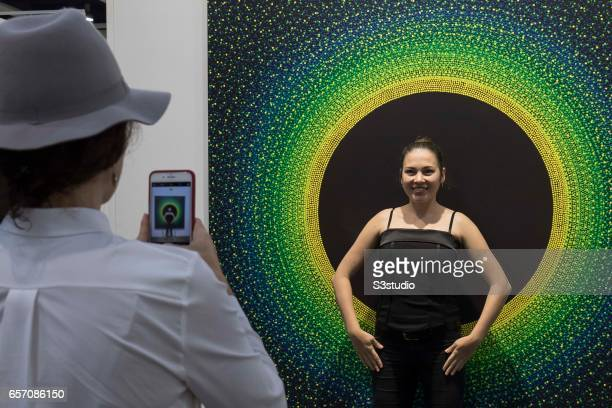 A visitor poses in front of artist Julio Le Parc's Alchimie 335 2016' during Art Basel Hong Kong 2017 at Hong Kong Convention and Exhibition Centre...