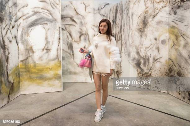 A visitor poses in front of artist Taroko Gorge's Cai GuoQiang 2009' during Art Basel Hong Kong 2017 at Hong Kong Convention and Exhibition Centre on...