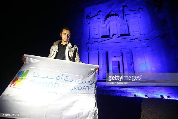 A visitor poses in front of the AlKhazneh or the Treasury illuminated in blue on April 2 2016 in Petra Jordan Major landmarks around the world will...