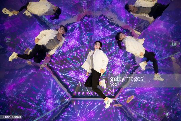 A visitor poses in the 'Kaleidoscope' installation at an experience centre on May 27 2019 in Hohhot Inner Mongolia Autonomous Region of China