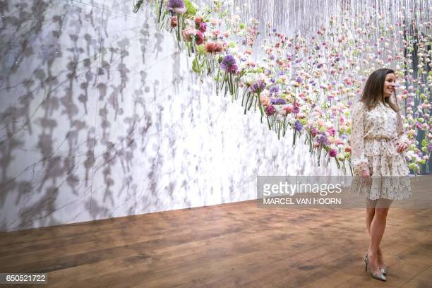 A visitor poses with a floral arrangement during the press preview of The European Fine Art Fair in Maastricht on March 9 2017 The TEFAF art and...