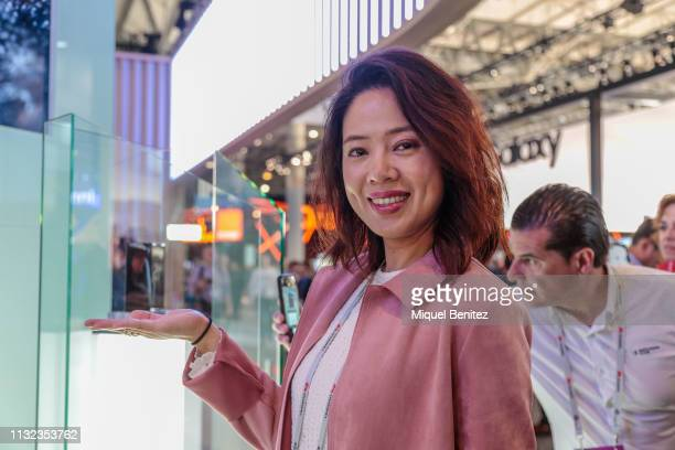 A visitor poses with a Huawei Mate X foldable phone during GSMA MWC 2019 The MWC2019 Mobile World Congress The presence of devices prepared to manage...