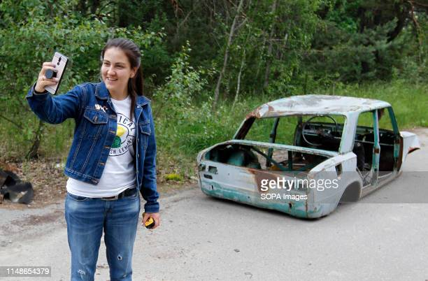 A visitor posses for a selfie next a wrecked car at the Chernobyl exclusion zone in the abandoned city of Pripyat The HBO television miniseries...