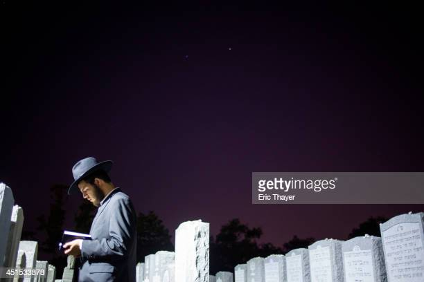 A visitor prays at the gravesite of the Lubavitcher Rebbe Rabbi Menachem Mendel Schneerson June 30 2014 at the Old Montefiore Cemetery in the Queens...