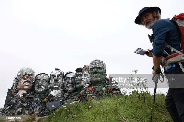 Visitor prepares to photograph a giant Mount Rushmore-style sculpture of the G7 leaders heads, made entirely of discarded electronics, is displayed...