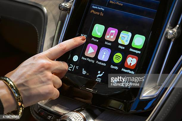 A visitor presses the new Apple's CarPlay touchscreen commands inside the Volvo Estate concept car displayed at the Swedish carmaker during the press...