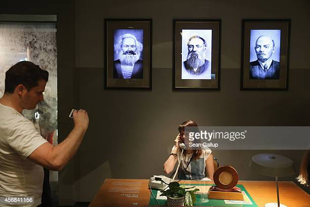 A visitor pretends to make a phone call at the desk of a communist party bureaucrat under portraits of Karl Marx Friedrich Engels and Vladimir Ilyich...