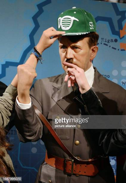 A visitor puts a basecap onto the wax figure of Adolf Hitler in the wax museum Madame Tussauds in London Great Britain 15 September 2013 Hitler is...