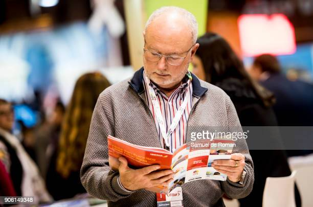 Visitor reading a leaftlet at FITUR International Tourism Fair 2018 at Ifema on January 17 2018 in Madrid Spain Prime Minister Mariano Rajoy...