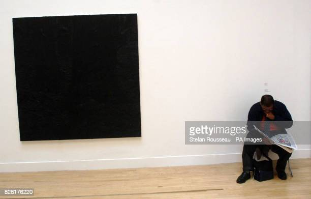 A visitor reads a newspaper alongside 'Black Square' an entry by Gillian Carnegie at the press launch for this year's Turner Prize at Tate Britain...