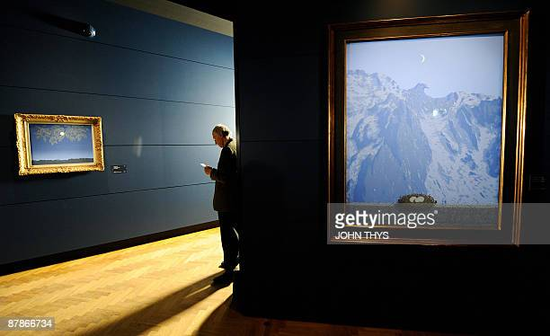 A visitor reads information about a painting by the Belgian artiste Rene Magritte displayed at the press opening of the new Margitte museum in...