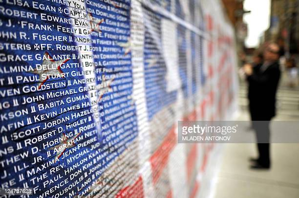 A visitor reads the names and of 9/11 terrorist attack victims on a wall outside Ground Zero memorial in Manhattan on September 10 2011 New York...
