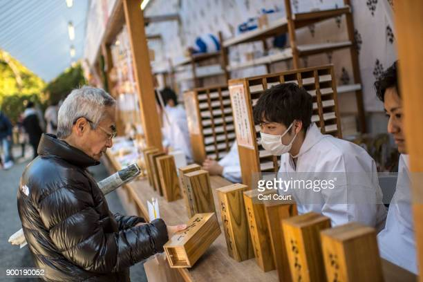 A visitor receives his 'omikuji' fortunetelling paper strips after praying for the new year at Tsurugaoka Hachimangu Shinto shrine on January 1 2018...