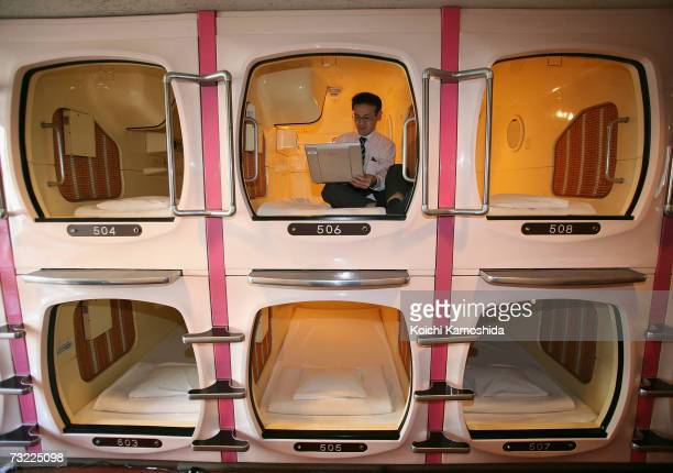 A visitor relaxes in a sleeping module at Tokyo's tube Hotel Capsule Inn Akihabara on February 6 2007 in Tokyo Japan The twosquaremeter sleep modules...