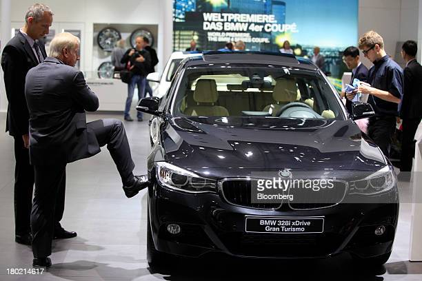 A visitor rests his foot on the wheel of a BMW 328i xDrive Gran Turismo SUV automobile produced by Bayerische Motoren Werke AG at the 65th Frankfurt...