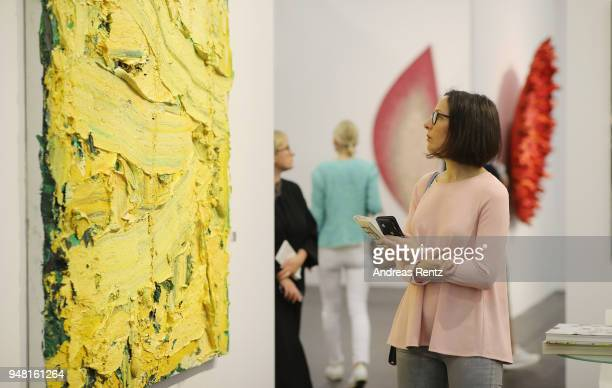 A visitor reviews an artwork at Pearl Lam Galleries booth during the Art Cologne exhibition preview at Koelnmesse on April 18 2018 in Cologne Germany...