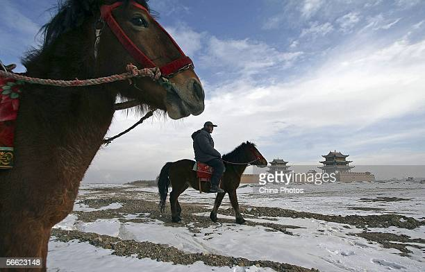 Visitor rides near the Jiayuguan Pass of the Great Wall after snowfall on January 18, 2006 in Jiayuguan of Gansu Province, northwest China. The Great...