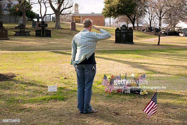 A visitor salutes at the Texas State Cemetery grave of US Navy Seal sniper Chris Kyle near the Texas State Capitol Kyle the most prolific sniper in...