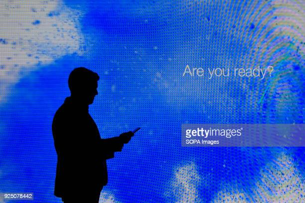 A visitor seen using his mobile phone in front of the large Samsung display screen at the Mobile World Congress The Mobile World Congress 2018 is...