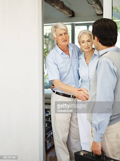 Visitor - Senior couple greeting a man at their door