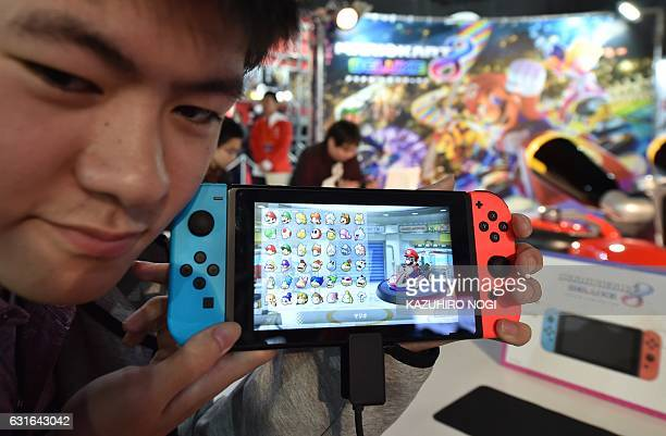 A visitor shows a Nintendo's new Switch game console during its game experience session in Tokyo on January 14 2017 Nintendo on January 13 unveiled...