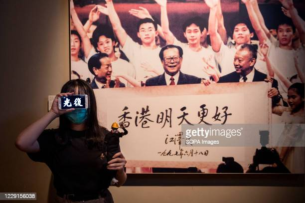 """Visitor shows a pro-democracy message on her phone in front of a portrait of former Chinese leader Jiang Zemin at the exhibition """"The Hong Kong..."""
