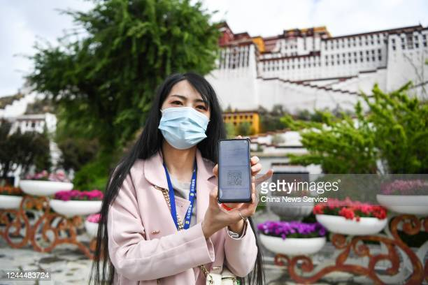 Visitor shows her e-ticket on her mobile phone with a QR code at the entrance of the Potala Palace on the first day of the reopening on June 3, 2020...