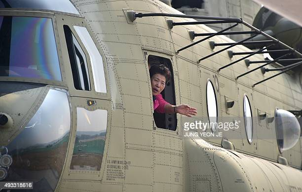 A visitor shows her face out of the window of a US Army CH47 Chinook helicopter during a media preview day of the Seoul International Aerospace and...