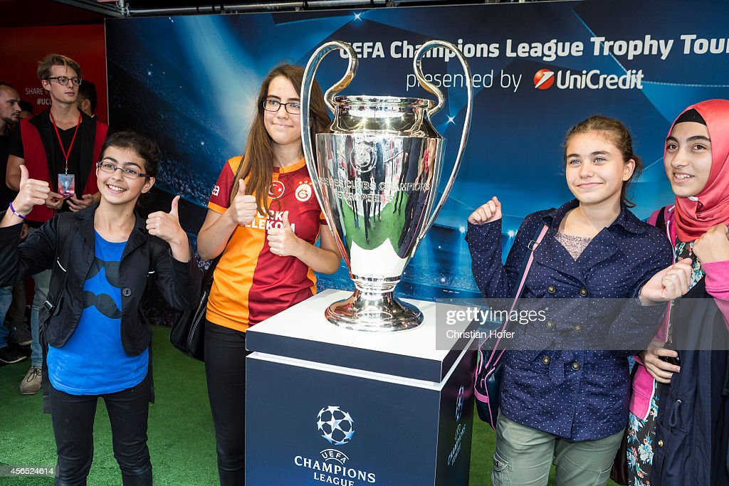 Visitor sieze the opportunity to have their picture taken while standing next to the UEFA Champions League Trophy during the Unicredit UEFA Champions League Trophy Tour on October 2 in Vienna, Austria.